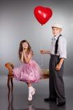 Il ragazzo dà un pallone rosso alla ragazza Immagine Stock