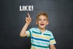 Il ragazzo davanti al consiglio scolastico con testo GRADISCE Immagini Stock