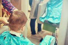 Il ragazzo del bambino al negozio di barbiere, ha tagliato i capelli immagine stock