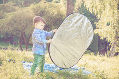Il ragazzo del bambino assiste il fotografo con il riflettore Immagine Stock Libera da Diritti