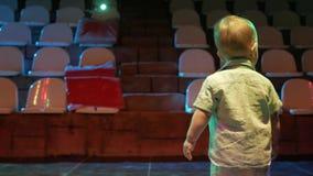 Il ragazzo del bambino che sta in mezzo alla scena ed è illuminato con proiettori Il bambino sveglio esamina il club e l'illumina archivi video