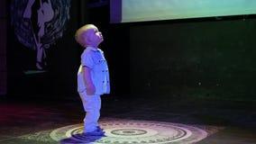 Il ragazzo del bambino che sta in mezzo alla scena ed è illuminato con proiettori Il bambino sveglio esamina il club e l'illumina stock footage
