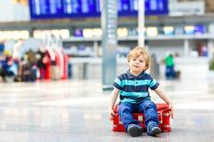 Il ragazzo del bambino che va sulle vacanze scatta con la valigia all'aeroporto Fotografia Stock