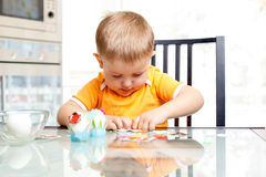Il ragazzo del bambino decora le uova di Pasqua all'interno Fotografia Stock Libera da Diritti