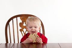 Il ragazzo del bambino esamina il biscotto con la bocca aperta Fotografia Stock