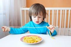 Il ragazzo del bambino ha fatto le perle dei maccheroni Immagini Stock