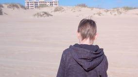 Il ragazzo del bambino sta camminando sulla spiaggia di sabbia alle dune di sabbia indietro osserva le attività di aria aperta stock footage