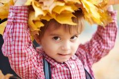 Il ragazzo del bambino sta posando con le foglie cadute gialle sulla sua testa Parco della città di autunno, giorno luminoso fotografia stock libera da diritti