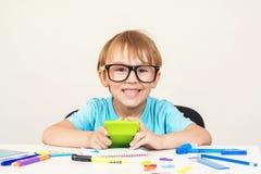 Il ragazzo del genio in vetri sta sedendosi allo scrittorio Ragazzo felice che fa compito a casa Ragazzo abile sveglio nello stud fotografie stock libere da diritti