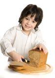 Il ragazzo del liitle che che affetta un pane sullo scrittorio Fotografie Stock