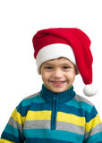 Il ragazzo del tempo di Natale con Santa Claus Hat ha isolato su bianco Immagine Stock