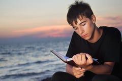 Il ragazzo dell'adolescente legge il libro che si siede sulla spiaggia Immagine Stock