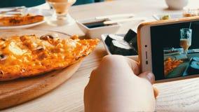 Il ragazzo dell'adolescente prende una foto di alimento su uno smartphone Rotoli di sushi giapponesi e pizza italiana sulla tavol archivi video