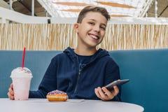 Il ragazzo dell'adolescente si siede alla tavola in caffè, beve il frappé, mangia la ciambella, tiene lo smartphone in sua mano I immagini stock