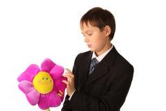 Il ragazzo dell'adolescente sta esaminando un fiore del giocattolo immagine stock