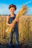 Il ragazzo dell'agricoltore felice con il covone Fotografia Stock