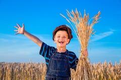 Il ragazzo dell'agricoltore felice sul giacimento di grano Immagini Stock
