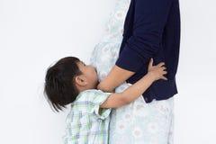 Il ragazzo della lettiera è abbracciante e baciante sua madre incinta fotografie stock