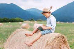 Il ragazzo della lettura si siede sopra il rotolo del mucchio di fieno sul giacimento della montagna dentro Immagini Stock Libere da Diritti