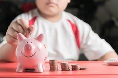 Il ragazzo della mano ha messo la moneta al porcellino salvadanaio, risparmiante i soldi Fotografia Stock Libera da Diritti