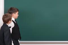 Il ragazzo della scuola elementare considera il fondo in bianco della lavagna, vestito in vestito nero classico, allievo del grup Immagine Stock Libera da Diritti