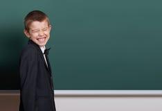 Il ragazzo della scuola elementare fa i fronti vicino al fondo in bianco della lavagna, vestito in vestito nero classico, un alli Fotografia Stock Libera da Diritti