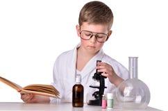 Il ragazzo dello scienziato nel laboratorio di chimica guarda nel mycroscope Immagine Stock