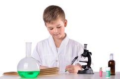 Il ragazzo dello scienziato nel laboratorio di chimica scrive con una penna Immagine Stock Libera da Diritti