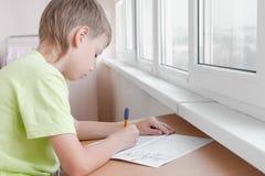 Il ragazzo dello scolaro impara scrivere le lettere che si siedono dalla tavola Fare lavoro immagini stock libere da diritti