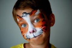 Il ragazzo di anni con gli occhi azzurri affronta la pittura di un gatto o di una tigre Arancio immagine stock libera da diritti