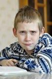 Il ragazzo di 10 anni con gli strappi negli occhi si siede prima del textb Fotografia Stock