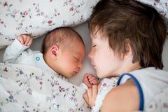 Il ragazzo di BBeautiful, abbracciando con la tenerezza e si preoccupa il suo bab neonato Immagine Stock Libera da Diritti
