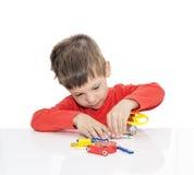 Il ragazzo di cinque anni si siede ad una tavola bianca e gioca un progettista elettronico Fotografie Stock
