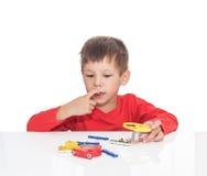 Il ragazzo di cinque anni si siede ad una tavola bianca e gioca un progettista elettronico Fotografia Stock