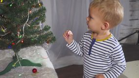 Il ragazzo di due anni che gioca con il Natale gioca sull'albero di Natale, fine su Ritratto di un bambino vicino ad un albero di stock footage