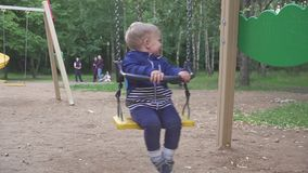 Il ragazzo di due anni sta guidando su un'oscillazione nel parco stock footage