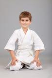 Il ragazzo di karatè in kimono bianco sta sedendosi Fotografia Stock
