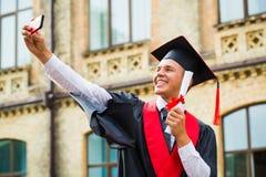 Il ragazzo di laurea prende un'immagine sul telefono cellulare Fotografia Stock Libera da Diritti