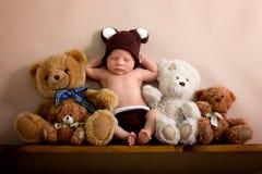 Il ragazzo di neonato che indossa un marrone ha tricottato il cappello dell'orso ed i pantaloni, sle immagini stock