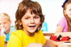 Il ragazzo di risata esamina diritto mentre si siede lo scrittorio Fotografie Stock