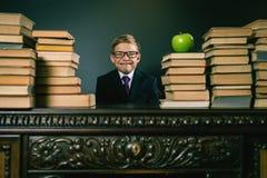 Il ragazzo di scuola abile che si siede alla tavola con molti prenota Fotografie Stock