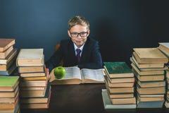 Il ragazzo di scuola abile che si siede alla tavola con molti prenota Immagini Stock Libere da Diritti