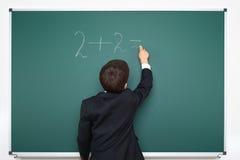 Il ragazzo di scuola decide il per la matematica di esempi sul fondo della lavagna, concetto dell'esame di istruzione Fotografia Stock Libera da Diritti