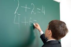 Il ragazzo di scuola decide il per la matematica di esempi sul fondo della lavagna, concetto dell'esame di istruzione Immagini Stock
