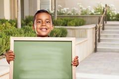 Il ragazzo di scuola ispano tiene il bordo di gesso in bianco sulla città universitaria della scuola Immagine Stock