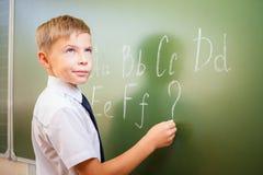 Il ragazzo di scuola scrive l'alfabeto inglese con gesso sulla lavagna Immagini Stock