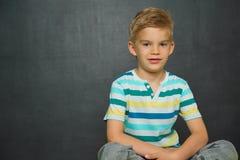 Il ragazzo di scuola sta stando con la lavagna dietro Fotografia Stock