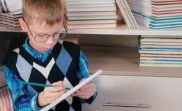 Il ragazzo di sette anni con i vetri che pensa e disegna qualcosa in uno sketchbook che si siede fra i libri Fotografie Stock