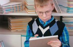 Il ragazzo di sette anni con i vetri disegna qualcosa in uno sketchbook che si siede fra i libri Fotografia Stock Libera da Diritti