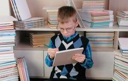 Il ragazzo di sette anni con i vetri disegna qualcosa in uno sketchbook che si siede fra i libri Immagini Stock